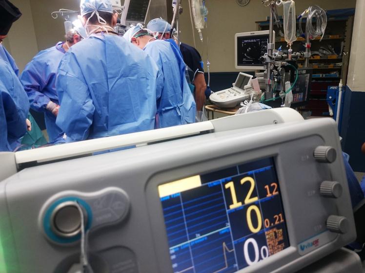 Ärzte in blauen Kitteln führen in einem Operationssaal eine Operation durch.