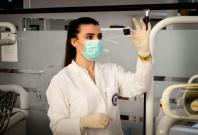 Ärztin mit Mundschutz prüft Gewebeprobe