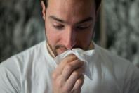 Ein Mann hält bedächtig ein Tuch vor die Nase.