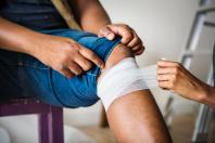 Mann bekommt einen Verband um das Bein gelegt.